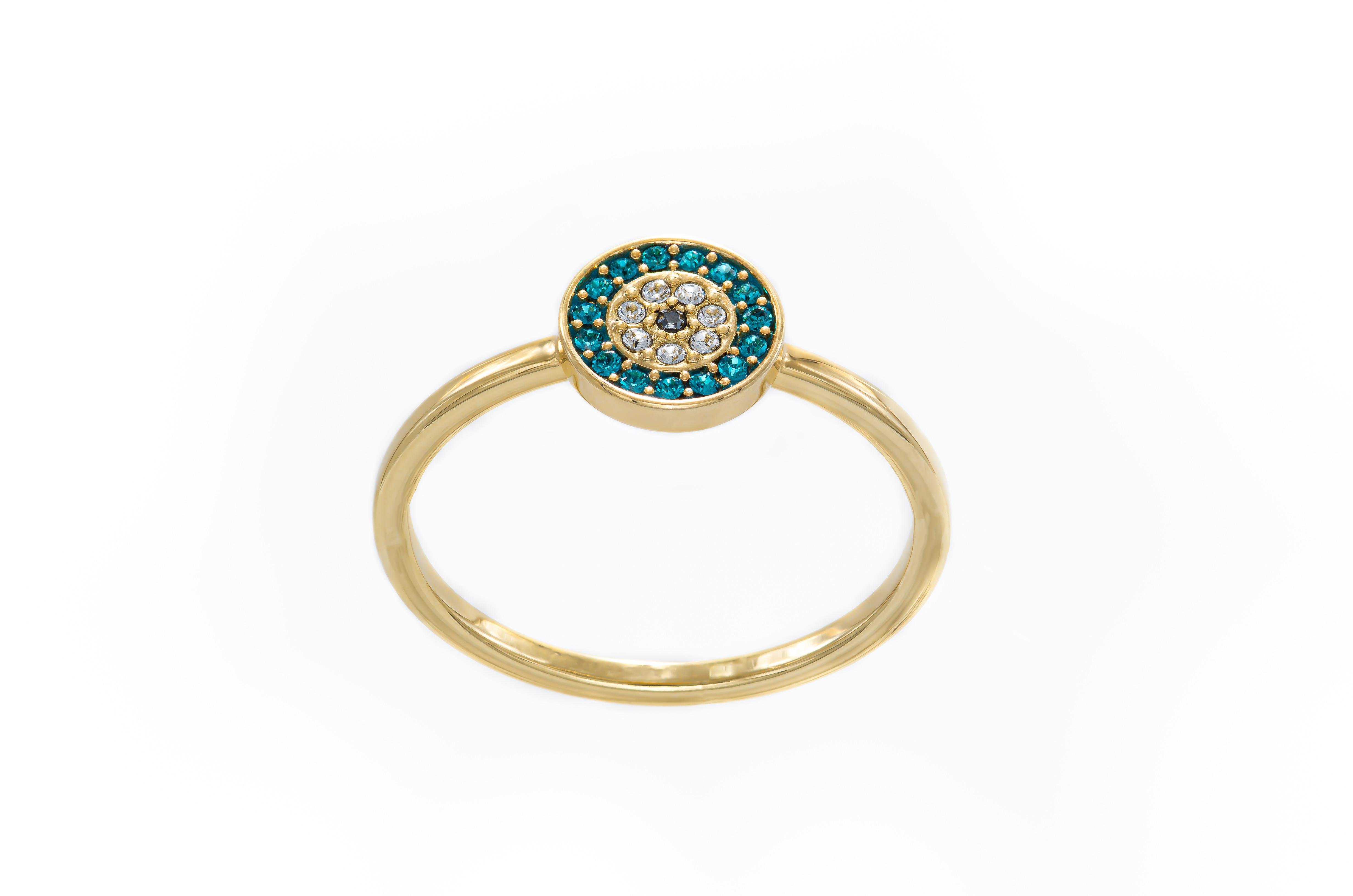 Fotografía de anillo de oro con piedras verdes