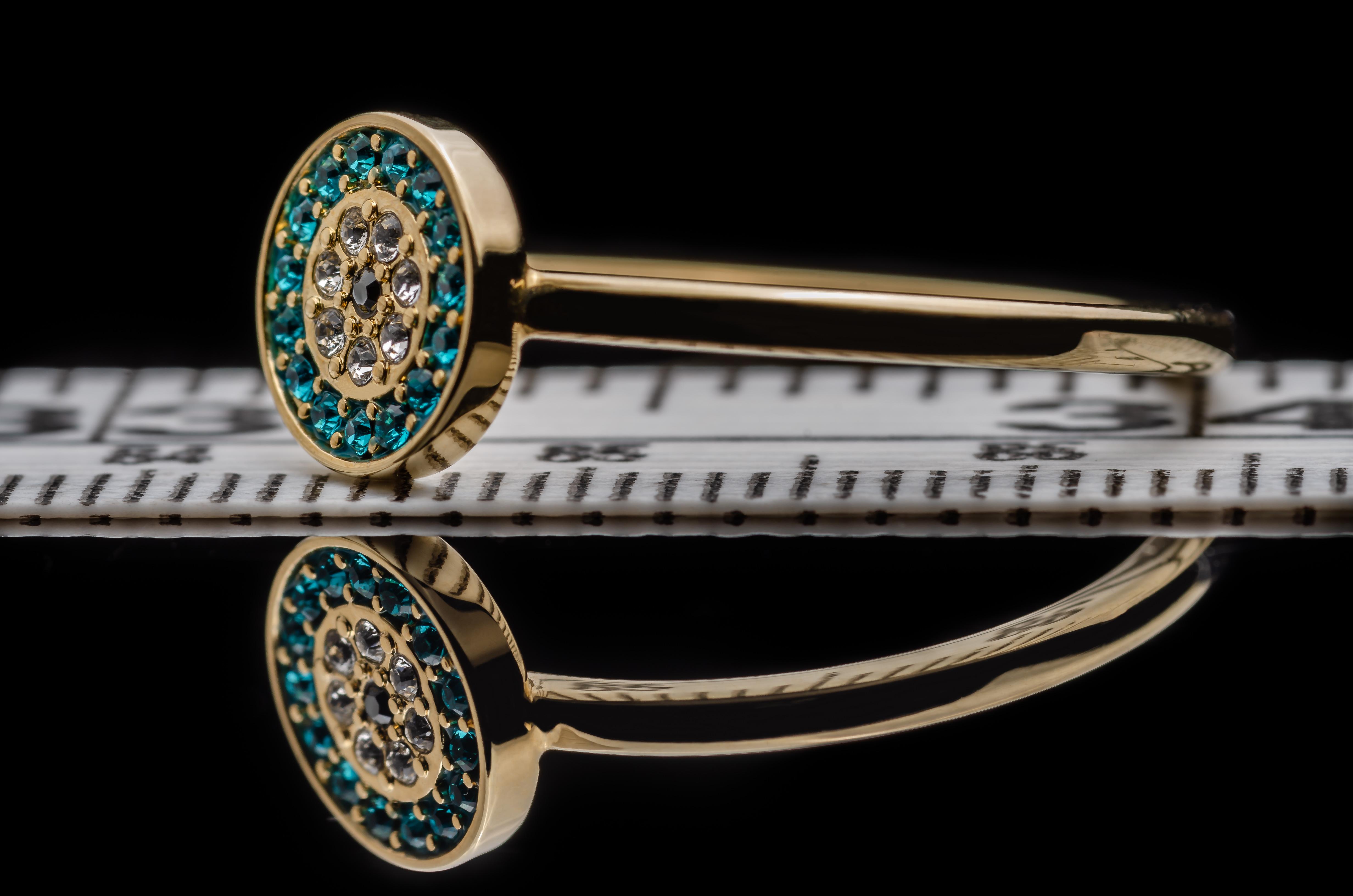 Fotografía de joyas, en la que se muestra un anillo, en fondo negro, situado sobre una cinta de costura para conocer sus tamaño y visualizar la profundidad de campo